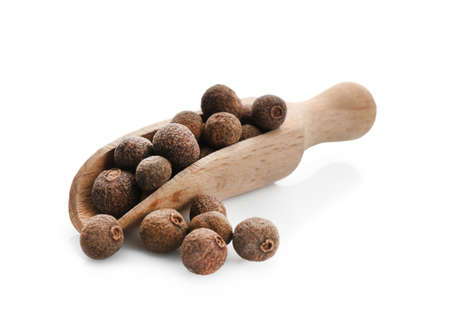 Wooden scoop with allspice pepper grains on white background