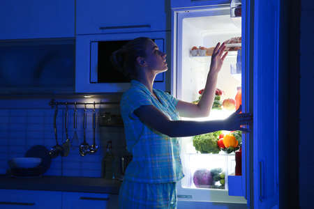 Woman choosing food from refrigerator in kitchen at night