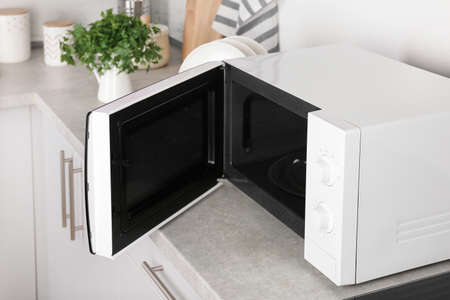 Open modern microwave oven on table in kitchen
