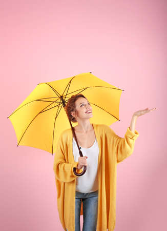 Woman with yellow umbrella on color background Archivio Fotografico