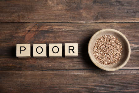 Bowl of buckwheat and cubes with word POOR on wooden background, top view