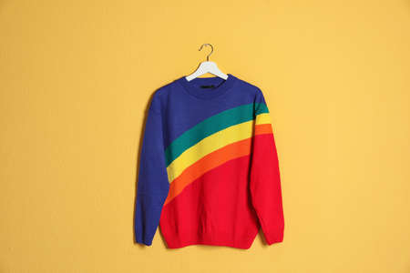 Hanger with stylish sweater on color background 스톡 콘텐츠
