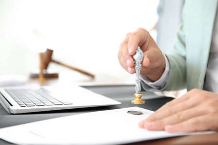 Male notary stamping document at table in office, closeup Stock Photo