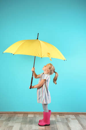 Little girl with yellow umbrella near color wall background