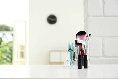 Organizzatore con prodotti cosmetici per il trucco sul tavolo al chiuso. Spazio per il testo