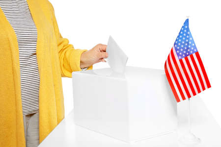 Elderly woman putting ballot paper into box against white background, closeup