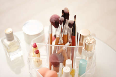 Makeup cosmetic products and tools in organizer on dressing table, closeup