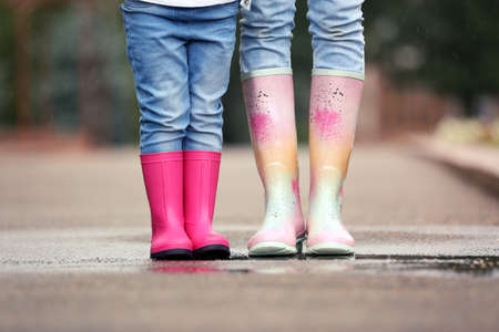 Mother and daughter wearing rubber boots on street, closeup Banque d'images