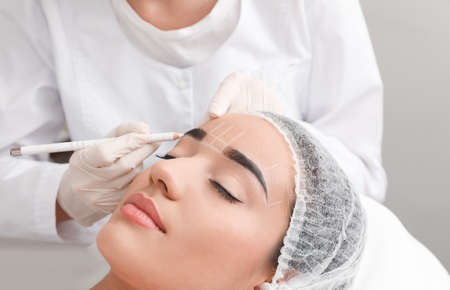 Young woman getting prepared for procedure of permanent eyebrow makeup in tattoo salon