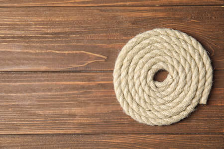 Hemp rope on wooden background, top view. Space for text
