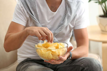 Man with bowl of potato chips sitting on sofa, closeup