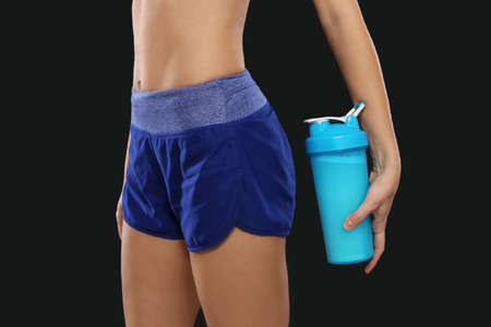 Woman with bottle of protein shake on black background