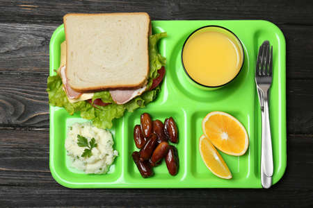 Tray with healthy food for school child on wooden background, top view