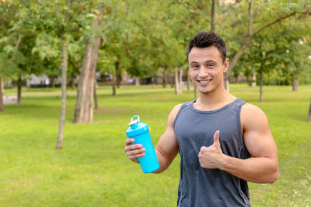 Man with bottle of protein shake in park. Space for text Stockfoto