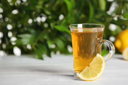 Glass cup of hot tea with lemon on white table