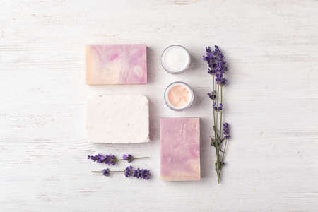 Flat lay composition with handmade soap bars and ingredients on white wooden background 版權商用圖片