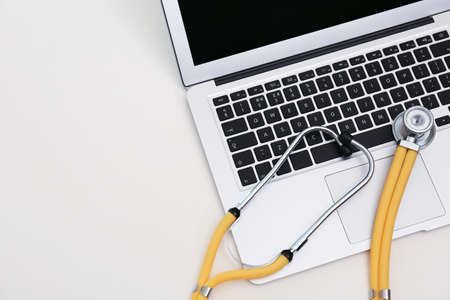 Modern laptop and stethoscope on table, space for text. Technical support concept