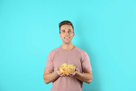 Man with bowl of potato chips on color background Stock Photo