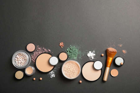 Flat lay composition with various makeup face powders on dark background. Space for text