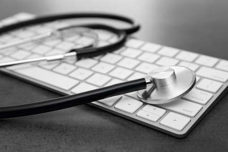 Modern keyboard and stethoscope on table. Technical support concept Zdjęcie Seryjne