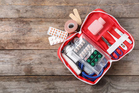Flat lay composition with first aid kit and space for text on wooden background Foto de archivo - 110810219