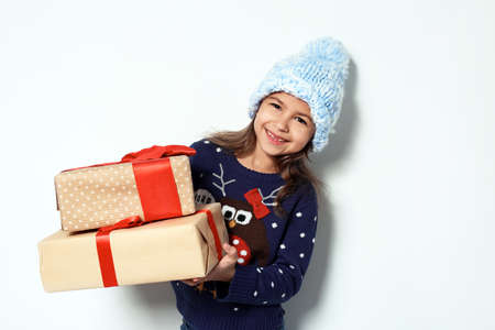 Cute little girl in Christmas sweater and knitted hat holding gifts on white background