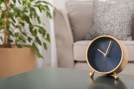 Stylish analog clock on table in living room, space for text. Time of day