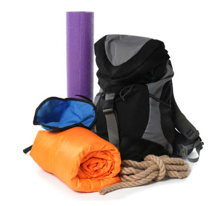 Sleeping bag, backpack and camping equipment on white background