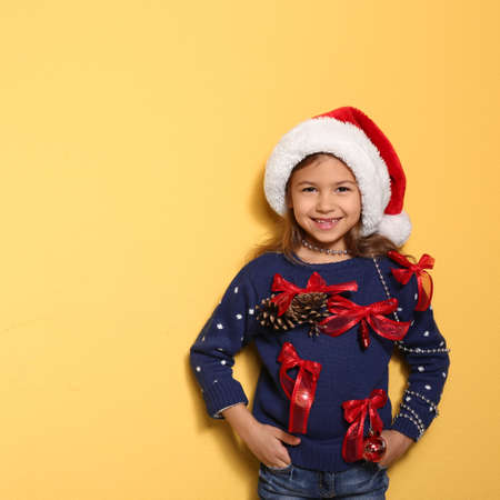 Cute little girl in handmade Christmas sweater on color background. Space for text