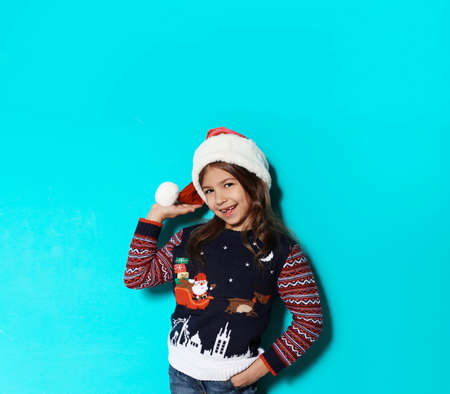 Cute little girl in Christmas sweater and hat on color background