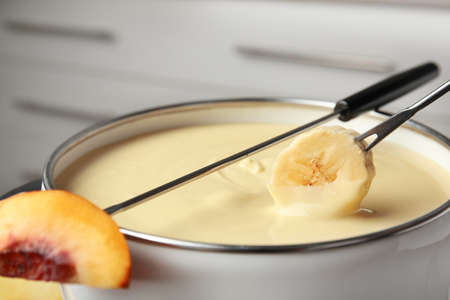 Dipping fresh banana into pot with chocolate fondue, closeup