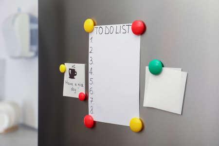 Paper sheets, to do list and magnets on refrigerator door indoors 版權商用圖片