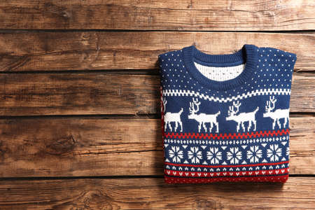 Christmas sweater with pattern and space for text on wooden background, top view