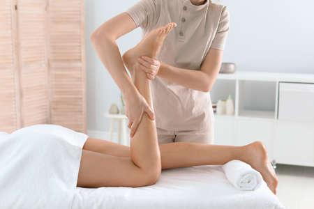 Vrouw ontvangt beenmassage in wellnesscentrum Stockfoto
