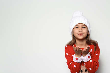 Cute little girl in Christmas sweater and knitted hat on white background. Space for text Foto de archivo