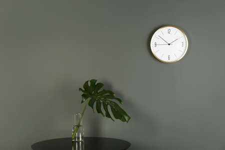 Analog clock on grey wall indoors. Time of day