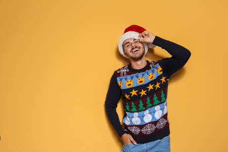 Young man in Christmas sweater and hat on color background. Space for text Imagens - 111301485