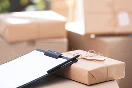 Clipboard, parcel with tag and blurred stacked boxes on background, indoors Stock Photo