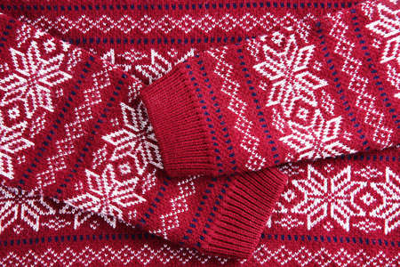 Christmas sweater with pattern as background, top view. Seasonal clothing Reklamní fotografie
