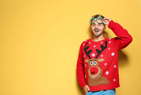 Young man in Christmas sweater with party glasses on color background. Space for text