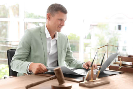 Male notary working with laptop at table in office