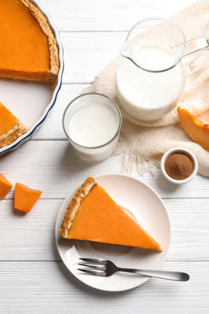 Flat lay composition with piece of fresh delicious homemade pumpkin pie on wooden background