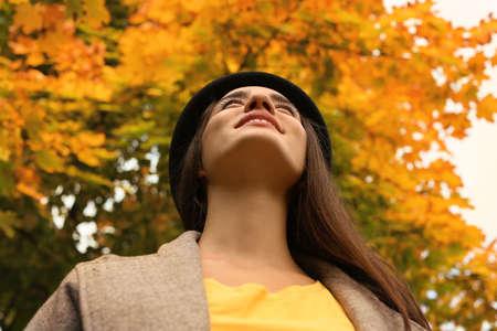 Belle jeune femme avec chapeau dans le parc, vue d'en bas. Promenade d'automne