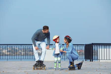 Patinaje sobre ruedas familia feliz en terraplén. Ocio activo