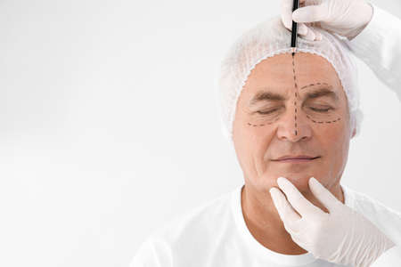 Doctor marking senior man face before cosmetic surgery on white background. Space for text Stock Photo