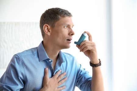 Joven con inhalador para el asma en casa Foto de archivo