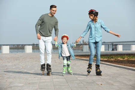 Patinaje sobre ruedas familia feliz en terraplén. Ocio activo Foto de archivo