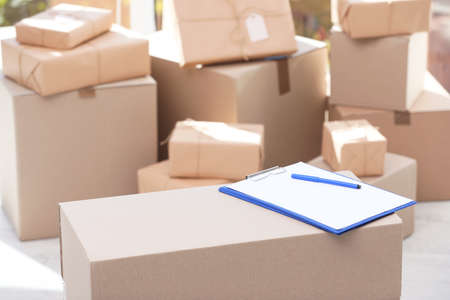 Clipboard, cardboard box and blurred stacked parcels on background, indoors 스톡 콘텐츠