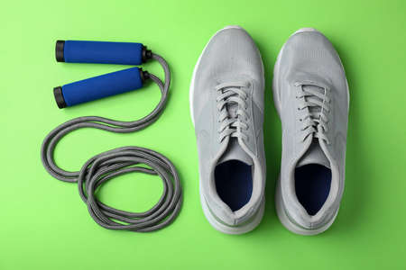 Jump rope and sneakers on color background. Healthy lifestyle Reklamní fotografie