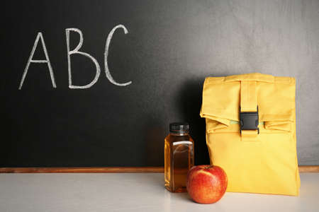 Healthy food for school child in lunch bag on table near blackboard with chalk written letters Standard-Bild